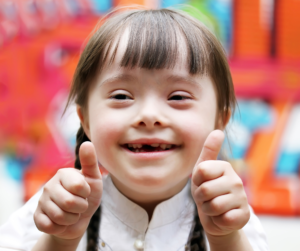 young-down-syndrome-girl-smiling-with-thumbs